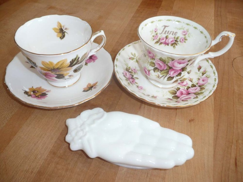 Two bone china tea cups and saucers and an Avon milk glass hand.