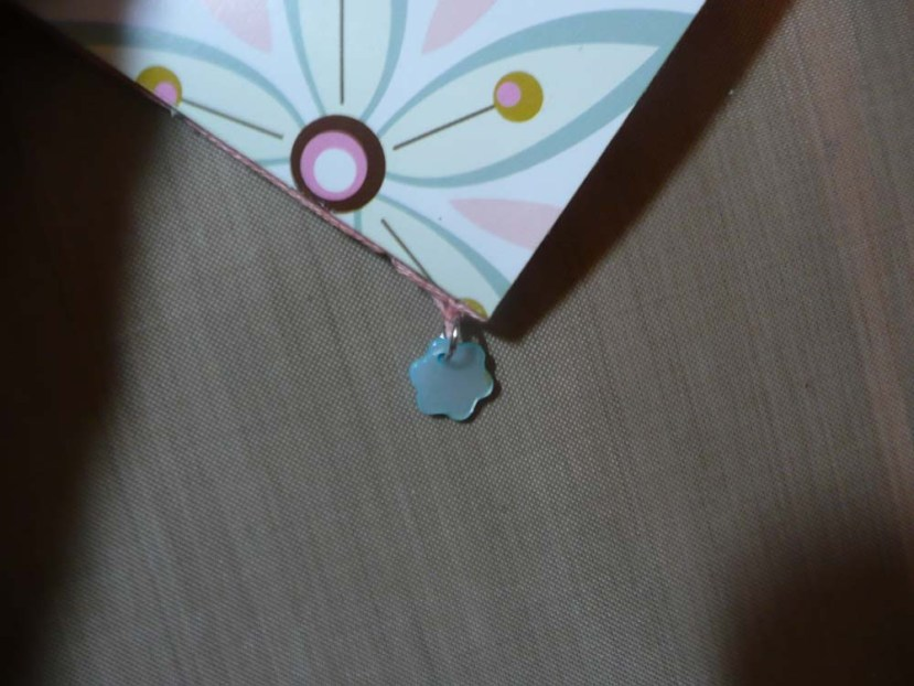 The sewed up spine with a little blue flower charm.