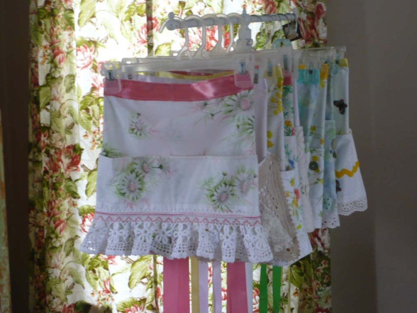 Lots of vintage fabric half aprons.