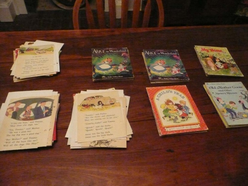 Sorting paper and ephemera into piles, each with a book cover.
