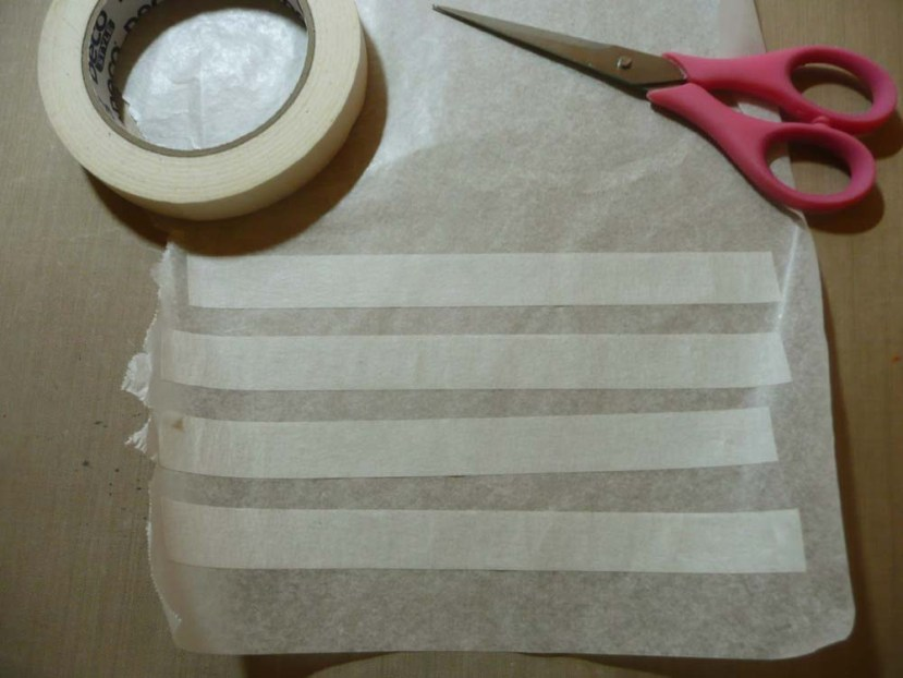 Pieces of masking tape on wax paper ready for stamping.