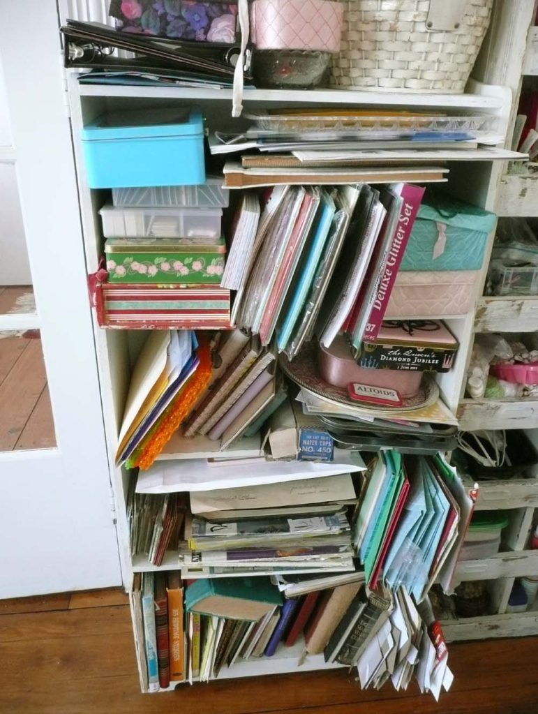 Shelf full of card stock, stencils, journals, and books and files of ephemera.