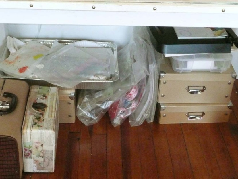 Under my desk are paper collections, paper pads and suitcases full of embellishments.