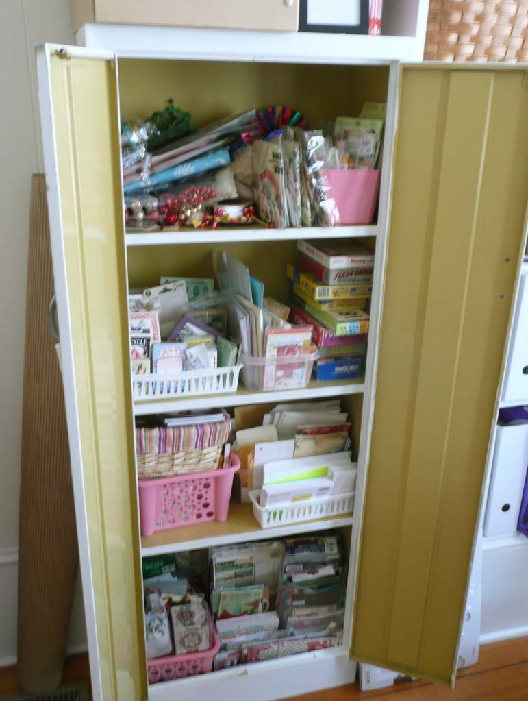 A vintage cabinet stuffed to the gills with items for making Junk Journals and Christmas projects.