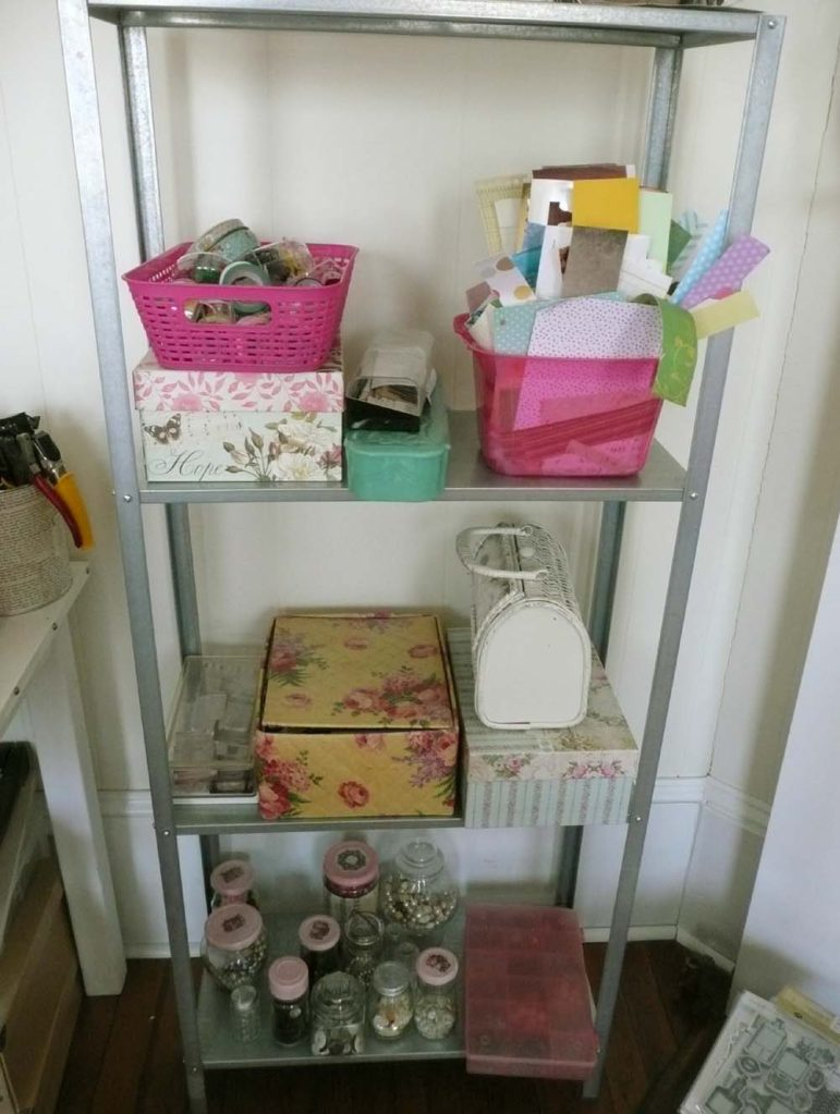 """A metal shelf from Ikea filled with stamps, scrap paper, beads, lace and other """"stuff""""."""